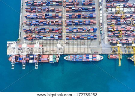 container ship in import export and business logistic. By crane Trade Port Shipping. Tugboat assisting cargo to harbor. Aerial view.