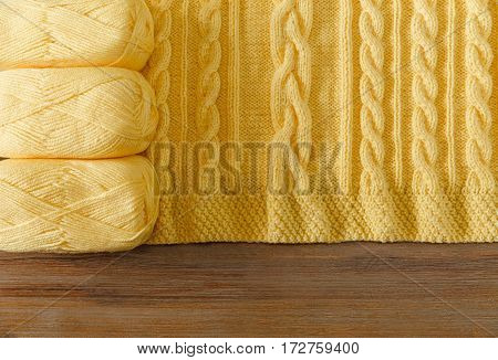 Yellow Knitted Items.Yellow Balloons of Yarn on the Wooden Table.Hand Made;Fancywork.