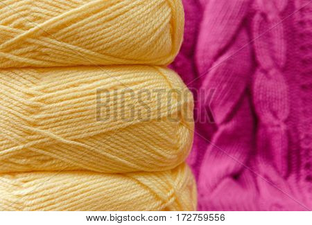 Yellow Balloon of Yarn on the Pink Knitted Item Background.Hand Made;Fancywork.Selective Focus