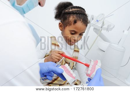 dentist tells African girl child how to properly brush their teeth. Oral hygiene. African-American, dentistry, tooth decay