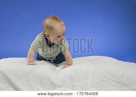Curious little baby boy on the white blanket, studio shot, isolated on blue background.