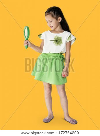 A girl is holding green magnifier