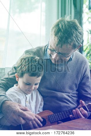 Grandfather teaching little cute grandson to play ukulele