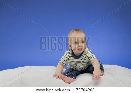 Funny little baby boy, sitting on the white blanket, studio shot, isolated on blue background.