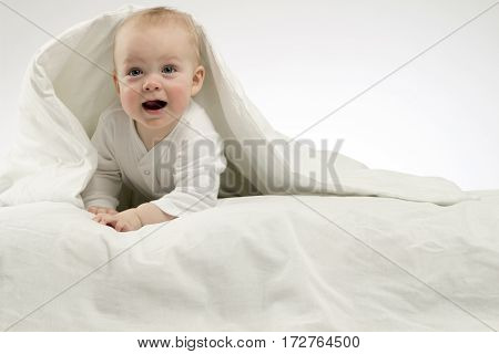 Suprised funny child under white blanket, studio shot, isolated, white background.
