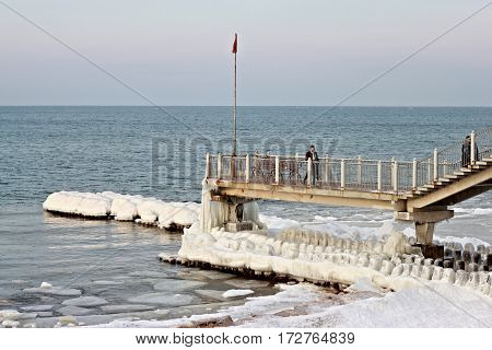 SVETLOGORSK, KALININGRAD REGION, RUSSIA - FEBRUARY 27, 2011: Tourists on a long jetty looking the Baltic Sea in the popular russian resort of Svetlogorsk (Rauschen) on a sunny winter day.