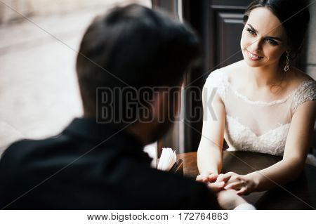 Lovely wedding photo, brunette bride and bridegroom sitting together near window and holding hands.