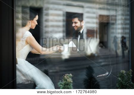 Lovely wedding photo, brunette bride and bridegroom sitting together behind big window and holding hands.
