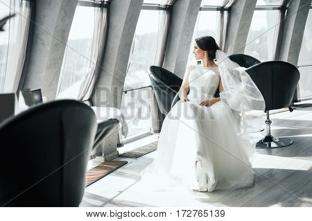 Gorgeous bride in white wedding dress sitting near big window, looking left, copy space, portrait.