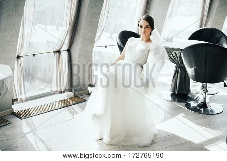 Beautiful brunette bride in wedding white dress, looking at camera, portrait, copy space.