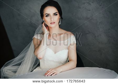 Beautiful bride with black hair in white dress at gray background, looking at camera, portrait, copy space.