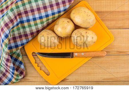 Raw Potatoes, Kitchen Knife On Plastic Cutting Board
