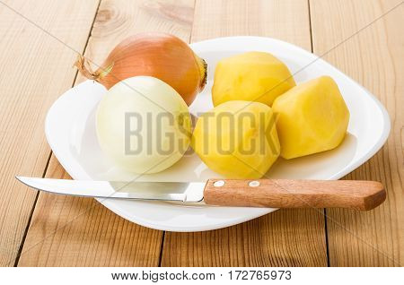 Peeled Raw Potatoes, Onion In Plate, Kitchen Knife On Table