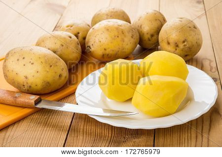 Peeled Raw Potatoes In Plate, Orange Cutting Board And Knife