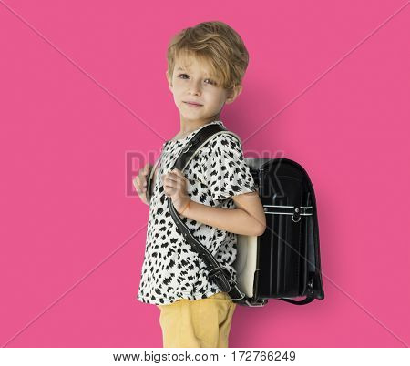 Young blonde boy carrying a backpack portrait