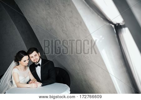 Beautiful wedding photo, brunette bride and bridegroom sitting together at gray background and hugging, portrait.