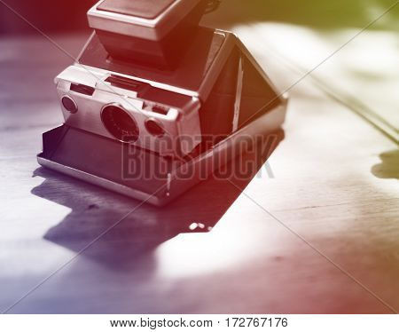 Vintage retro instant photo camera on the wooden table