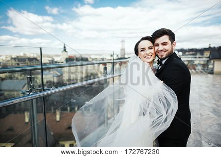 Brunette brunette bride and bridegroom standing close to each other at old city background and smiling, wedding photo, looking at camera.