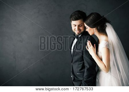 Beautiful brunette bride and bridegroom standing close to each other at gray background and smiling, wedding photo, copy space.