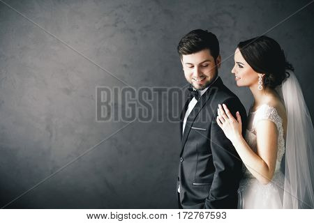 Pretty brunette bride and bridegroom standing close to each other at gray background and smiling, wedding photo, portrait.