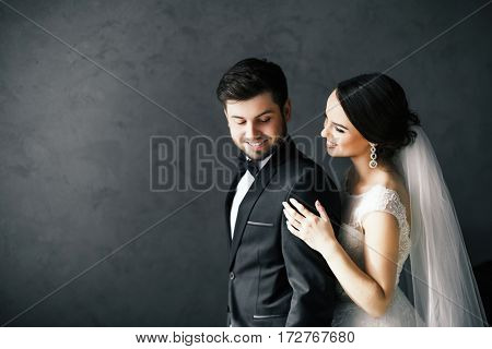 Beautiful brunette bride and bridegroom standing close to each other at gray background and smiling, wedding photo.