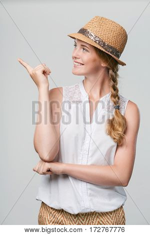 Beautiful smiling woman wearing summer straw fedora hat pointing finger to the side at blank copy space