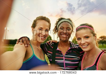 Smiley multicultural group of 3 girls takes a group photo at sunrise in the park after their high intensity strenght training session