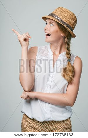Happy surprised woman wearing summer straw fedora hat pointing finger to the side at blank copy space