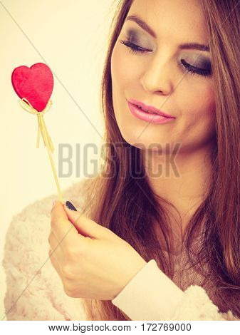 Flirty Woman Holding Red Wooden Heart On Stick