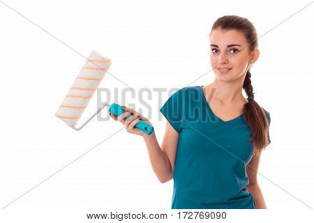young beautiful brunette woman builder in uniform with paint roller in hands make reovations and posing on camera isolated on white