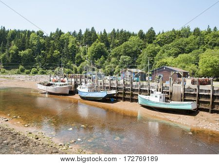 The view of small boats docked in St. Martins village during the low tide (New Brunswick Canada).