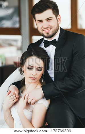 Lovely wedding photo, brunette bride and bridegroom sitting together, looking at camera and smiling, portrait, holing hands.
