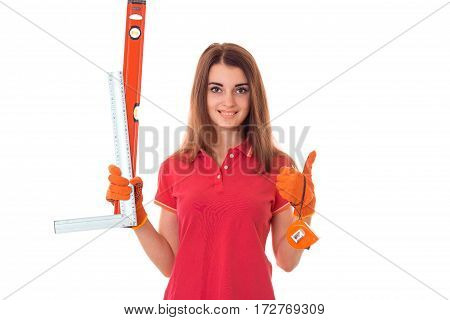 young happy brunette woman builder in uniform with tools in her hands make reovations isolated on white