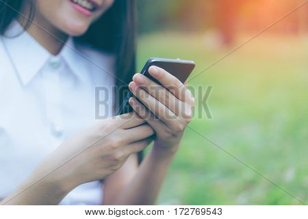 Beautiful Young asian woman smiling while reading her smartphone in garden. Portrait of asian women reading message with smart phone in park outdoor.
