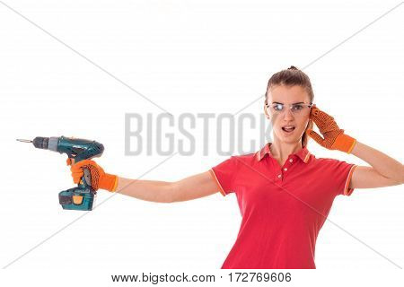 young funny brunette woman builder in uniform with glasses and drill in her hands make reovations isolated on white