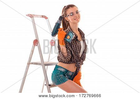young happy brunette woman builder in uniform with glasses and drill in her hands make reovations isolated on white