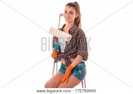 young attractive brunette woman builder in uniform with paint roller in her hands make reovations isolated on white
