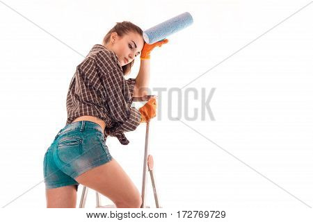 sexy tired brunette woman builder in uniform with paint roller in her hands make reovations isolated on white