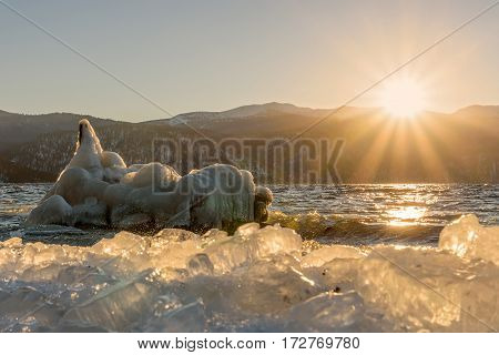 Beautiful winter landscape with a lake the sun iceberg on the water and ice on the bank on the background of mountains at dawn