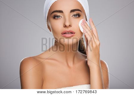 Gorgeous girl with brown hair fixed behind, clean fresh skin, big eyes and naked shoulders wearing white bandage, posing at gray studio background with cleaning sponge near face.