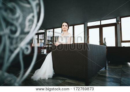 Pretty brunette bride in wedding white dress, sitting and looking at camera, portrait, copy space.