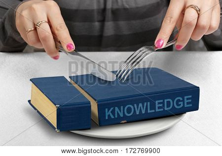 consume knowledge concept cut book on plate