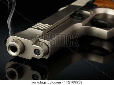 Closeup of handgun with smoke barrel on black soft focus