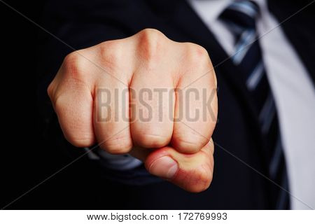 Clenched fist of business man aiming for the camera