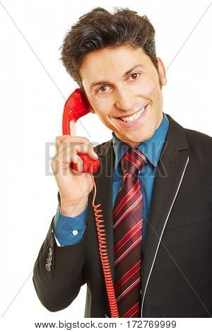 Smiling business man making phone call with a red telephone