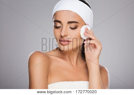 Beautiful girl with brown hair fixed behind, clean fresh skin, big eyes and naked shoulders wearing white bandage, posing at gray studio background with cleaning sponge near face, close up.