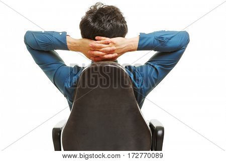 Business manager sitting in office chair with his hands behind his head