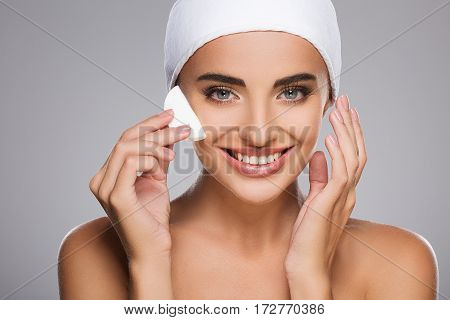 Smiling girl with brown hair fixed behind, clean fresh skin, big eyes and naked shoulders wearing white bandage, posing at gray studio background with cleaning sponge near face.
