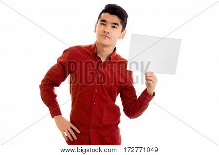 youn attractive brunette male model in red shirt posing with empty placard in his hands and looking at the camera isolated on white