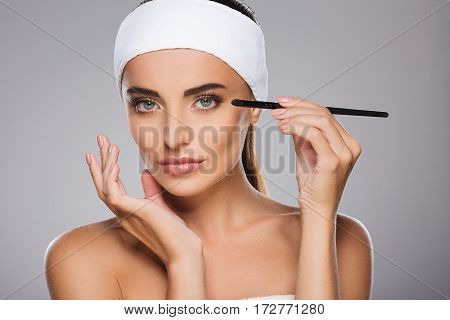 Young girl with brown hair fixed behind, clean fresh skin, big eyes and naked shoulders wearing white bandage, doing make up at gray studio background.